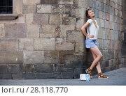 Купить «Young woman standing on stone wall background», фото № 28118770, снято 15 августа 2017 г. (c) Яков Филимонов / Фотобанк Лори