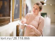 Купить «Attractive girl holding guide book in museum», фото № 28118866, снято 18 ноября 2017 г. (c) Яков Филимонов / Фотобанк Лори