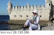 Купить «Female tourist studying a map of the route sitting on the stone edge near the Belem tower in Lisbon, Portugal», видеоролик № 28130386, снято 18 апреля 2017 г. (c) Алексей Кузнецов / Фотобанк Лори