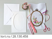 Купить «Needlework. Preparation of a gift card with an insert of a flower composition embroidered manually with satin ribbons. Felicitation on the spring holiday», фото № 28130458, снято 27 февраля 2018 г. (c) Виктория Катьянова / Фотобанк Лори