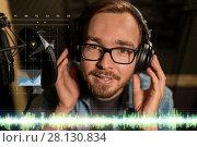 Купить «man with headphones singing at recording studio», фото № 28130834, снято 18 августа 2016 г. (c) Syda Productions / Фотобанк Лори