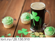 Купить «shamrock on glass of beer, green cupcakes and coins», фото № 28130910, снято 31 января 2018 г. (c) Syda Productions / Фотобанк Лори