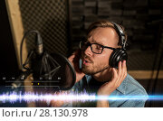 Купить «man with headphones singing at recording studio», фото № 28130978, снято 18 августа 2016 г. (c) Syda Productions / Фотобанк Лори