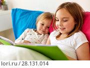 Купить «little girls or sisters reading book in bed», фото № 28131014, снято 15 октября 2017 г. (c) Syda Productions / Фотобанк Лори