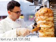 Купить «chef slicing doner meat from spit at kebab shop», фото № 28131082, снято 7 декабря 2017 г. (c) Syda Productions / Фотобанк Лори