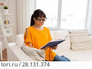 Купить «young asian woman in glasses reading book at home», фото № 28131374, снято 9 марта 2016 г. (c) Syda Productions / Фотобанк Лори