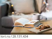 Купить «oat cookies, almonds and book on table at home», фото № 28131434, снято 15 ноября 2017 г. (c) Syda Productions / Фотобанк Лори