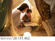 Купить «happy family reading book in kids tent at home», фото № 28131462, снято 27 января 2018 г. (c) Syda Productions / Фотобанк Лори