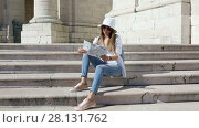 The girl tourist with map in hand resting on the steps of a temple in Lisbon, Portugal (2017 год). Стоковое видео, видеограф Алексей Кузнецов / Фотобанк Лори
