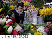 Купить «Женщина продает букеты весенних тюпанов на цветочном рынке в канун празднования Международного женского дня 8 Марта в городе Москве, Россия», фото № 28139022, снято 7 марта 2018 г. (c) Николай Винокуров / Фотобанк Лори