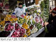 Купить «Мужчина продает букеты весенних тюпанов на цветочном рынке в канун празднования Международного женского дня 8 Марта в городе Москве, Россия», фото № 28139070, снято 7 марта 2018 г. (c) Николай Винокуров / Фотобанк Лори