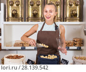 Купить «Girl seller is demonstraiting Macadamia in bag», фото № 28139542, снято 4 сентября 2017 г. (c) Яков Филимонов / Фотобанк Лори