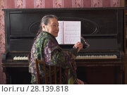 Купить «Old lady pianist seating at the piano», фото № 28139818, снято 20 февраля 2018 г. (c) Константин Шишкин / Фотобанк Лори