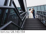 Beautiful couple newlyweds on a metal staircase. Стоковое фото, фотограф Чебеляев Геннадий / Фотобанк Лори
