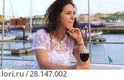 Купить «Lovely young Caucasian woman drinking red wine sitting in a cafe outdoors with a great views of the bay with yachts», видеоролик № 28147002, снято 18 июня 2017 г. (c) Алексей Кузнецов / Фотобанк Лори