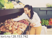 Купить «Smiling young woman customer examining various onions», фото № 28153742, снято 23 ноября 2016 г. (c) Яков Филимонов / Фотобанк Лори