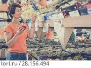 Купить «Smiling female is choosing apples in the supermarket.», фото № 28156494, снято 22 октября 2017 г. (c) Яков Филимонов / Фотобанк Лори