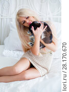 Купить «Pretty young blonde embraces fluffy black rabbit on white bed in room», фото № 28170670, снято 20 ноября 2015 г. (c) Losevsky Pavel / Фотобанк Лори