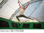 Купить «MOSCOW, RUSSIA - AUG 29, 2016: Happy girl (with model release) jumps on trampoline in center Just Jump in Sokolniki park. Trampoline Arena is suitable for both adults and children athletes and fans.», фото № 28170690, снято 29 августа 2016 г. (c) Losevsky Pavel / Фотобанк Лори