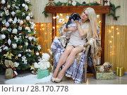 Купить «Attractive blonde holds bunny during sits on chair near christmas tree and garlands», фото № 28170778, снято 20 ноября 2015 г. (c) Losevsky Pavel / Фотобанк Лори