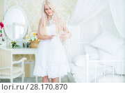 Купить «Young woman in white dress touches white hanger in cozy bedroom», фото № 28170870, снято 20 ноября 2015 г. (c) Losevsky Pavel / Фотобанк Лори