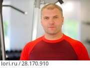 Купить «Young strong man smiles in modern gym with fitness equipment», фото № 28170910, снято 30 июня 2016 г. (c) Losevsky Pavel / Фотобанк Лори