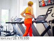 Купить «Middle-aged woman in orange runs on treadmill in modern gym, back view», фото № 28170930, снято 1 июля 2016 г. (c) Losevsky Pavel / Фотобанк Лори