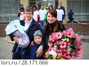 Купить «Man with newborn, girl, woman with flowers stand near maternity hospital, nine people out of focus», фото № 28171066, снято 22 марта 2016 г. (c) Losevsky Pavel / Фотобанк Лори