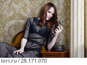 Купить «Pretty young woman in black poses with retro phone in room», фото № 28171070, снято 20 ноября 2015 г. (c) Losevsky Pavel / Фотобанк Лори
