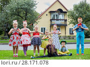 Купить «Five girls and three boys in bright dancing suits stand and sit on grassy lawn against two-storied house showing hearts with their hands», фото № 28171078, снято 10 сентября 2016 г. (c) Losevsky Pavel / Фотобанк Лори