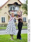 Купить «Boy and girl in dancing suits dance on grassy lawn against two-storied house», фото № 28171086, снято 10 сентября 2016 г. (c) Losevsky Pavel / Фотобанк Лори