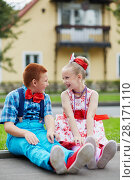 Smiling boy and girl in bright dancing suits sit on road curb and look at each other against two-storied house. Стоковое фото, фотограф Losevsky Pavel / Фотобанк Лори