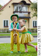 Купить «Little boy in dancing suit plays saxophone and little girl dances on grassy lawn against two-storied house», фото № 28171118, снято 10 сентября 2016 г. (c) Losevsky Pavel / Фотобанк Лори