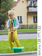 Купить «Little boy in dancing suit plays saxophone on grassy lawn against two-storied house near road, hat for earnings lies on grass», фото № 28171122, снято 10 сентября 2016 г. (c) Losevsky Pavel / Фотобанк Лори