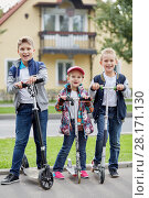 Купить «Two boys and girl stand with push scooters on road against two-storied house», фото № 28171130, снято 10 сентября 2016 г. (c) Losevsky Pavel / Фотобанк Лори