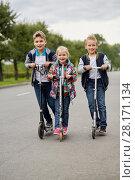 Купить «Two boys and girl ride on push scooters on road», фото № 28171134, снято 10 сентября 2016 г. (c) Losevsky Pavel / Фотобанк Лори