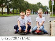 Купить «Two smiling boys and girl sit on skateboards on road», фото № 28171142, снято 10 сентября 2016 г. (c) Losevsky Pavel / Фотобанк Лори