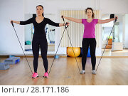 Купить «Woman and girl in sport wear trains with elastic band for fitness in modern gym», фото № 28171186, снято 25 марта 2016 г. (c) Losevsky Pavel / Фотобанк Лори