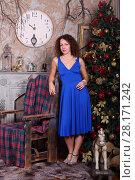 Купить «Beautiful woman in blue dress poses near Christmas fir tree and fireplace in studio», фото № 28171242, снято 27 ноября 2015 г. (c) Losevsky Pavel / Фотобанк Лори