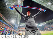 MOSCOW, RUSSIA - SEP 9, 2016: Fan (with model release) with red-and-blue scarf with CSKA MOSKOW inscription at new CSKA Arena sports complex stadium during match between CSKA and Terek soccer teams. Редакционное фото, фотограф Losevsky Pavel / Фотобанк Лори