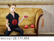 Купить «Teenage girl sits on couch holding half of pomegranate in her hand», фото № 28171454, снято 9 декабря 2015 г. (c) Losevsky Pavel / Фотобанк Лори