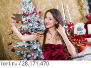 Купить «Young smiling woman makes selfie in room decorated to christmas holidays», фото № 28171470, снято 9 декабря 2015 г. (c) Losevsky Pavel / Фотобанк Лори
