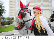 Купить «Laughing woman stands with horse in harness near buildings, coachman sits on couch», фото № 28171478, снято 17 сентября 2016 г. (c) Losevsky Pavel / Фотобанк Лори