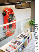Купить «MOSCOW - APR 16, 2016: Hyundai Solaris on wall and magazines in Hyundai Motorstudio. Hyundai produces not only cars, but also its own collection of furniture and household items», фото № 28171518, снято 16 апреля 2016 г. (c) Losevsky Pavel / Фотобанк Лори