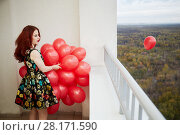 Купить «Young smiling red-haired woman holds in hand bunch of red balloons and leaves one to fly standing at balcony of highrise building», фото № 28171590, снято 15 октября 2015 г. (c) Losevsky Pavel / Фотобанк Лори