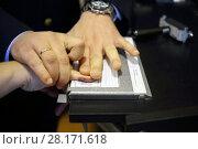 Купить «Hands of two men during fingerprinting, text translate - dactyloscopic registration, pinky», фото № 28171618, снято 22 сентября 2016 г. (c) Losevsky Pavel / Фотобанк Лори