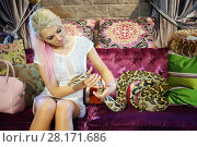 Купить «Beautiful woman in white sits with big snake on purple sofa in room», фото № 28171686, снято 18 июля 2016 г. (c) Losevsky Pavel / Фотобанк Лори
