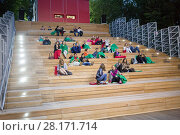 MOSCOW, RUSSIA - JUN 30, 2015: People sitting on wooden staircase of Open Air Cinema in Sokolniki. Редакционное фото, фотограф Losevsky Pavel / Фотобанк Лори