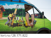 MOSCOW, RUSSIA - JUL 4, 2015: Male legs out the windows in car with nature print. Редакционное фото, фотограф Losevsky Pavel / Фотобанк Лори
