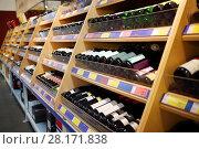Купить «Many wine bottles are on wooden shelves at modern alcohol store», фото № 28171838, снято 27 апреля 2016 г. (c) Losevsky Pavel / Фотобанк Лори